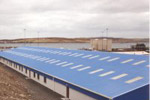 Translucent roof sheeting, lots of windows, personnel doors. Typical of this type of factory building